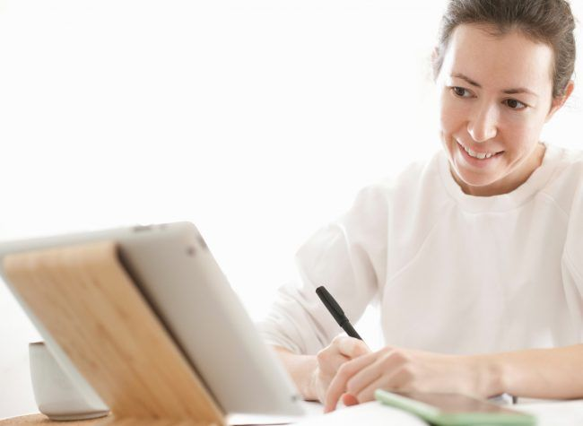 a-female-student-studying-online-looking-at-tablet-T7DKPNS